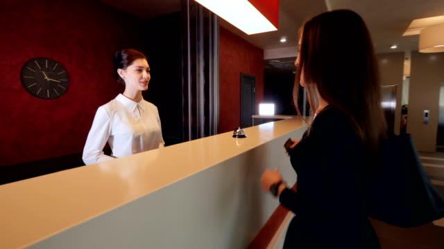 Mujer atractiva en vestíbulo de recepción. Viajar de vacaciones con equipaje. - vídeo