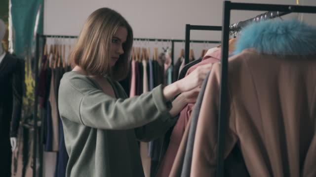 vídeos de stock, filmes e b-roll de mulher atraente escolha elegante casaco na loja - boutique
