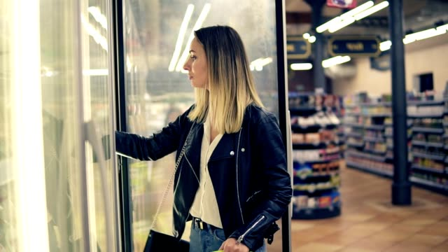attractive woman choosing the dairy products in the supermarket in refrigerator. young woman takes frozen products to a shop basket. side view - замороженные продукты стоковые видео и кадры b-roll