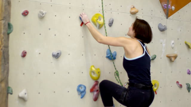 attraktive frau klettert aktiv auf indoor kletterwand - bouldering stock-videos und b-roll-filmmaterial