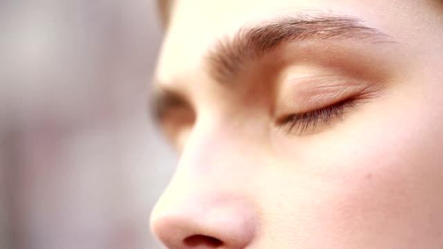 魅力的な女性は、目を閉じると笑顔します。女性の手は、アイシャドウとブラシを保持しています。女性の手がアップ彼女の目。 - アイシャドウ点の映像素材/bロール