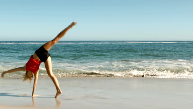 Attractive woman doing cartwheels on the beach  Attractive woman doing cartwheels on the beach in slow motion tank top stock videos & royalty-free footage