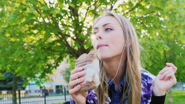 vídeos de stock e filmes b-roll de attractive woman eating a sandwich in the park, listening to music - sanduíche