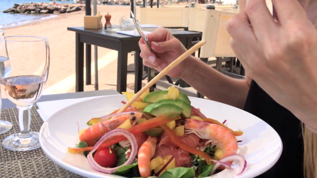 Attractive woman eating salad at beach restaurant video