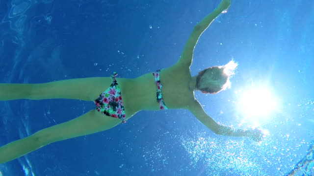 UNDERWATER CLOSE UP: Attractive woman floating on surface in crystal clear ocean video