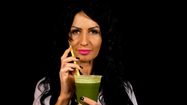 attractive woman healthy drinking and enjoying a green smoothie - healthy green juice video stock e b–roll
