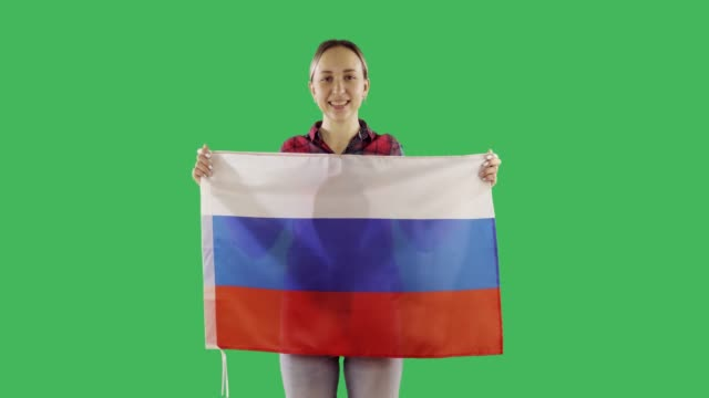 Attractive woman holds Russian flag in hands on chroma key green screen.