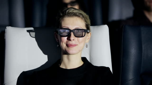Attractive woman in 3D glasses watching a movie at cinema video