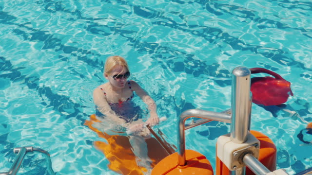 Attractive woman in a swimsuit doing exercises in the pool. Healthy lifestyle. Aqua aerobics in the open air video
