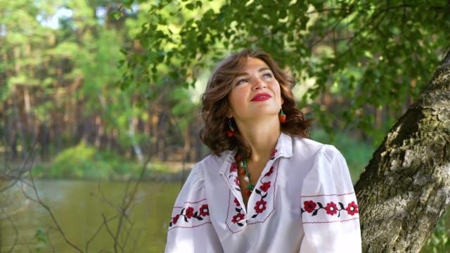 attractive woman in ethnic ukrainian dress sitting on birch tree near river - славянская культура стоковые видео и кадры b-roll