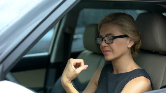 vídeos de stock, filmes e b-roll de mulher atraente em óculos sentado no carro, sofrendo de dor no pulso, saúde - articulação humana