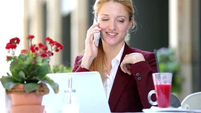 Attractive woman in the street restaurant talking on the phone and uses laptop. video