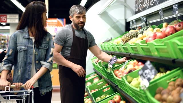 魅力的な女性の興味を持った顧客はセールスマンと話をハンサムな男フレンドリーなスーパー マーケットで果物の部署で働いている、女性は、新鮮なフルーツの臭いがします。 ビデオ
