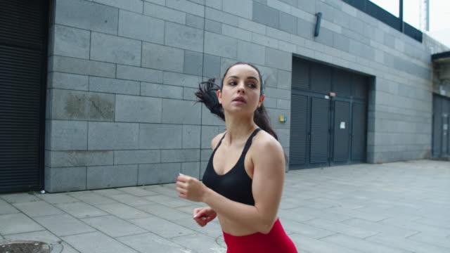 vidéos et rushes de femme attirant faisant le jogging à la rue de ville. fille sexy fonctionnant à l'entraînement extérieur. - joggeuse