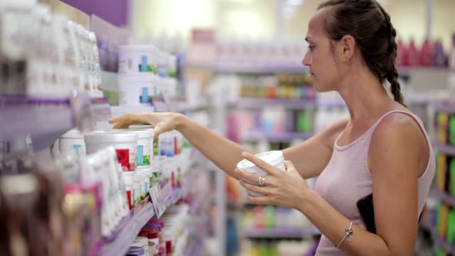 attractive woman looking body care products at cosmetics section in supermarket - igiene video stock e b–roll