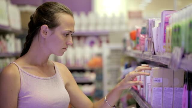 vídeos de stock, filmes e b-roll de mulher atraente procurando produtos de cuidado de corpo na seção de cosméticos no supermercado - skincare
