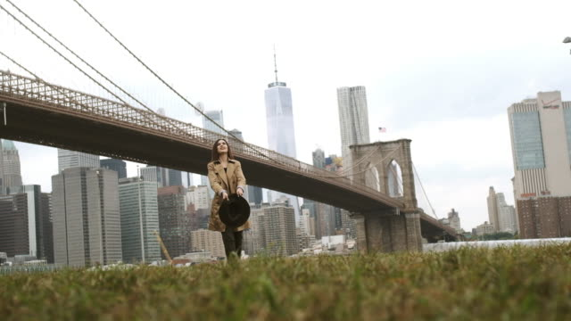 Attraktive Frau. Spielen mit einem stilvollen Hut. Brooklyn Bridge. – Video