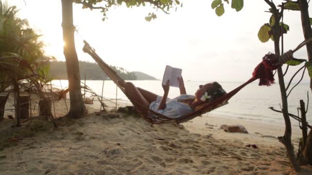 bella donna leggendo un libro su un'amaca - amaca video stock e b–roll