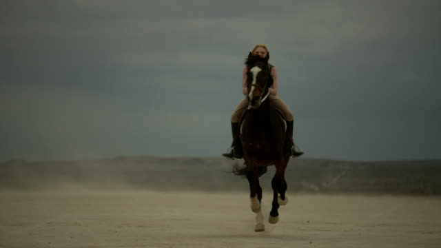(Slow Motion) Attractive Woman Riding Horse 06 A young attractive blonde woman rides a horse in slow motion across the desert planes. cowgirl stock videos & royalty-free footage