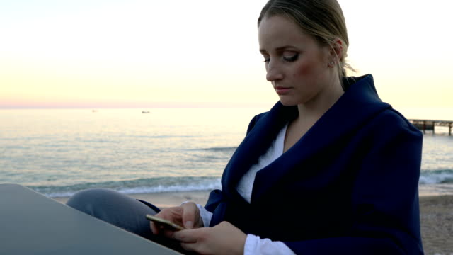 Attractive woman sitting at table in beach cafe sending message on mobile video