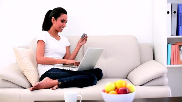 vídeos de stock e filmes b-roll de atraente mulher sentada no sofá usando o seu computador portátil - coffee table