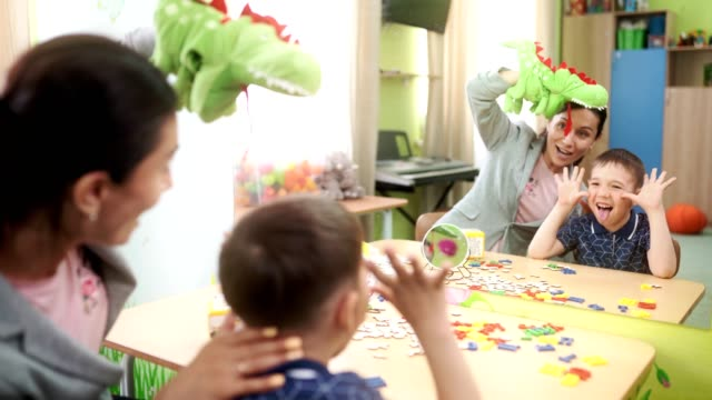 A attractive woman speech therapist and a preschool boy are having fun at a speech therapy session The attractive woman speech therapist teaches the preschool aged boy to correctly pronunciation a letters and a words. The boy is doing the tongue exercise and making funny faces. The woman playing and helping the boy playroom stock videos & royalty-free footage