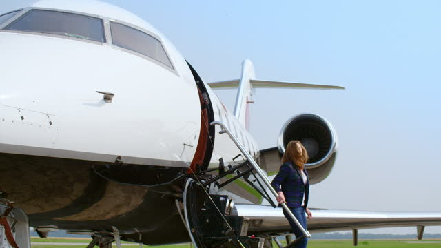 Attractive woman steps out of an executive jet video