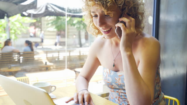 attractive woman talking on mobile phone and using laptop in coffee shop. - owner laptop smartphone video stock e b–roll