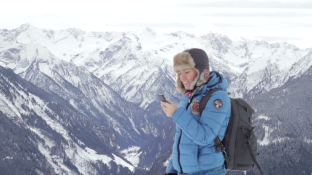 Attractive woman texting with her phone in the mountains video