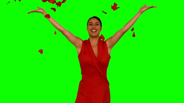 Attractive woman throwing red petals in the air video