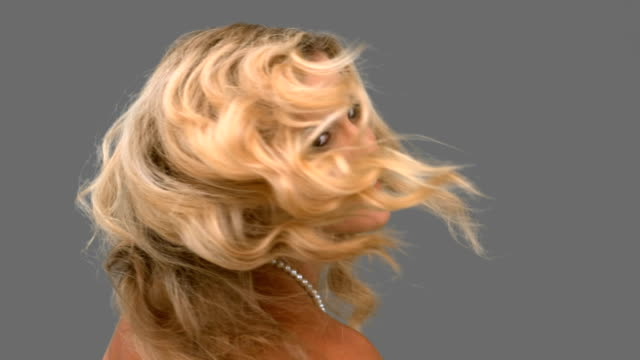 Attractive woman tossing her hair on grey screen video
