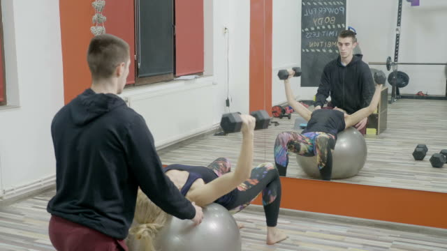Attractive woman using a pilates ball while working out her arms with dumbbells in a gym with her young personal instructor standing by video