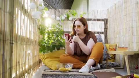 attractive woman using smartphone on terrace Attractive young woman blogger using modern smartphone chatting or have video call on light decorated terrace on sunny day boho stock videos & royalty-free footage