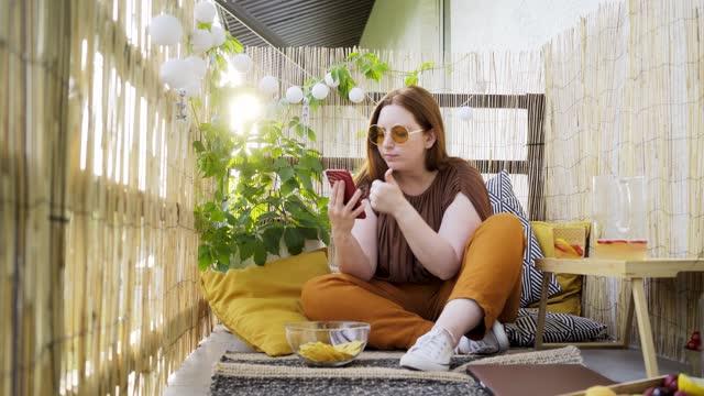 vídeos de stock, filmes e b-roll de mulher atraente usando smartphone no terraço - boho