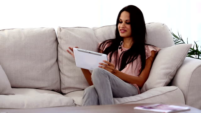 Attractive woman using tablet pc on the couch video
