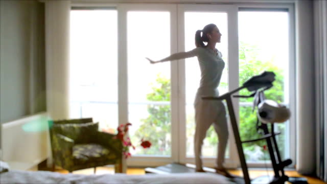 Attractive woman walks on a treadmill, is engaged in home video