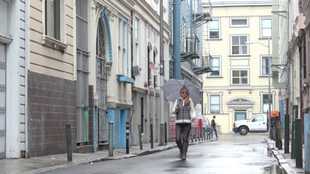 attractive woman with an umbrella is walking out into a charming alley on a rainy day. checking her mobile phone. - victorian architecture stock videos & royalty-free footage