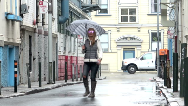 Attractive Woman with an umbrella is walking out into a charming alley on a rainy day. Checking her mobile phone. video