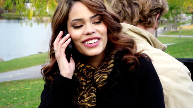 Attractive woman with cellphone in park video