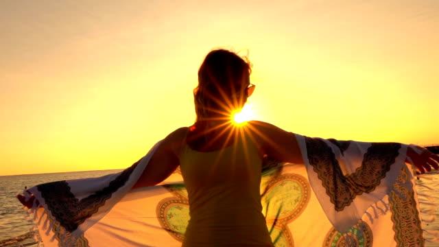 SLOW MOTION attraktive Frau mit flatternden Schal stehen am Strand bei Sonnenuntergang – Video