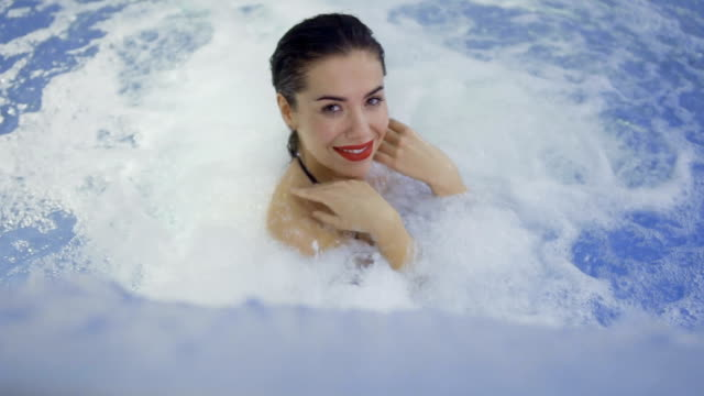attractive woman with red lips rejoices with water flow in swimming pool - rossetto rosso video stock e b–roll