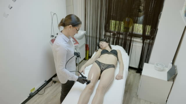 Attractive woman with sexy lingerie receiving cosmetic skincare weight loss and anti fat procedure on legs with medical tool at wellness clinic video