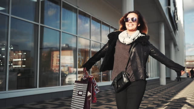 attractive woman with shopping bags enjoying their walk down the street video