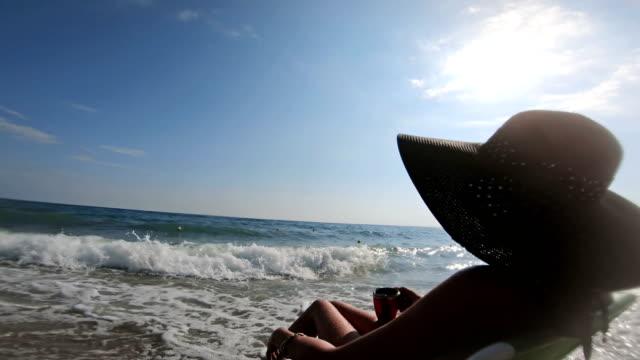 vídeos y material grabado en eventos de stock de atractiva mujer con sombrero de paja sentado en la playa junto al mar y disfrutando mientras las olas se estrellan en la orilla - espalda humana