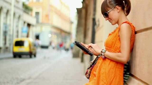 Attractive woman with tablet computer in the city, steadicam shot video