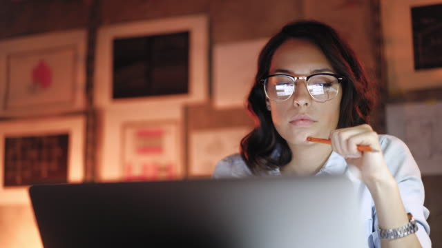 Attractive Woman working on laptop late at night