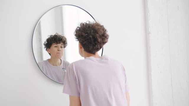 パジャマで魅力的な女性は、バスルームで鏡を見て歯を磨く - ブラシ点の映像素材/bロール