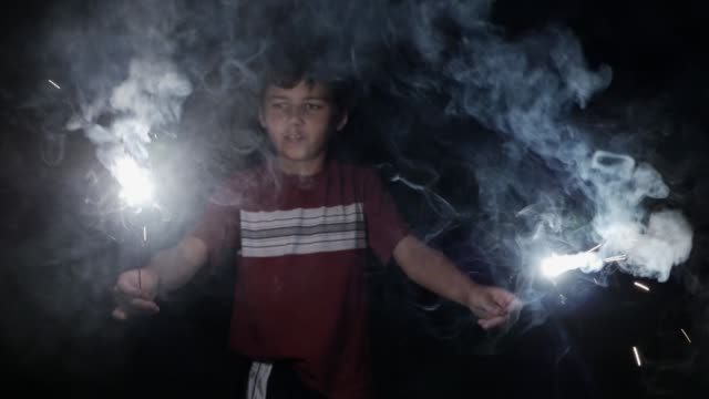 Attractive young 8 - 10 year old boy holding two burning sparklers and fireworks Attractive young 8 - 10 year old boy holding two burning sparklers and fireworks in his hands at night celebrating 4th of July Independence day holiday in slow motion family 4th of july stock videos & royalty-free footage
