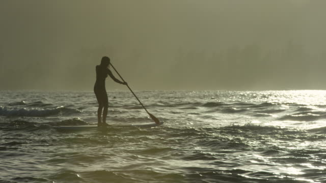 Attractive young adult female running into the ocean to go surfing video
