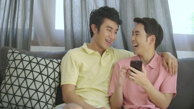 attraktive junge asiatische schwules paar zu hause entspannen, im gespräch und mittels smartphone zusammen mit glücklich emotion. - gay man stock-videos und b-roll-filmmaterial